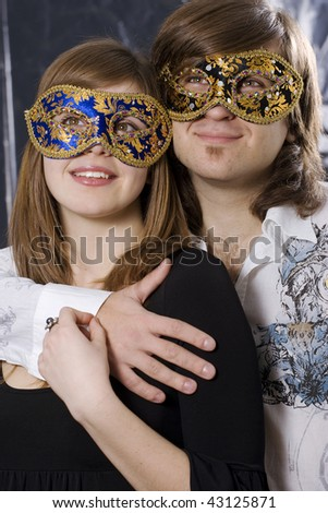 Happy beautiful young couple wearing masks looking up - stock photo