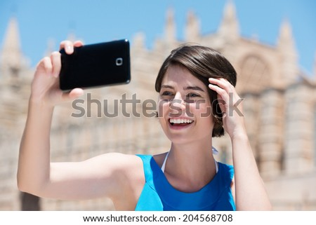 Happy beautiful young female tourist taking a selfie in Majorca posing in front of the cathedral holding up her mobile phone and laughing - stock photo