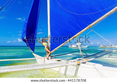 Happy beautiful young girl in bikini on a tropical beach on a sailboat. Blue sea in the background. Summer vacation concept.