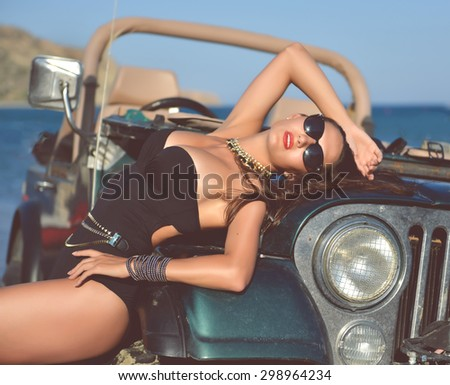 Happy beautiful young girl standing near beach truck car in sunglasses on sunny summer day - stock photo