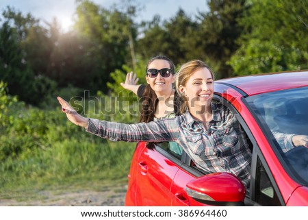 Happy beautiful young girls in a red car in the sunset. Travel concept. Concept of travel, rent or buying car.  - stock photo