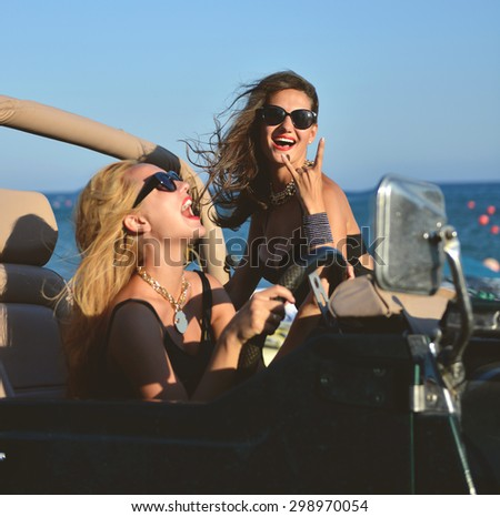 Happy beautiful young girls sitting laughing in beach truck car in sunglasses on sunny summer day.   - stock photo