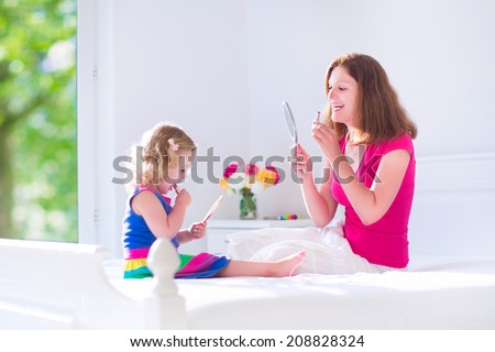 Happy beautiful young mother and her adorable daughter, cute little girl with curly hair applying make up, lipstick, looking into hand mirrors sitting on a white bed in a sunny bedroom with window - stock photo