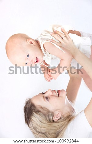 happy beautiful young mother holding her laughing little baby up isolated on white background in studio - stock photo