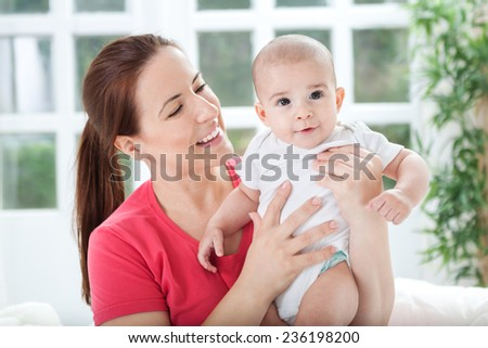 Happy beautiful young mother looking proudly to her child - stock photo