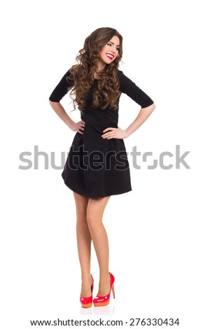 Happy beautiful young woman in black mini dress and red high heels posing with hands on hip and looking away. Full length studio shot isolated on white. - stock photo