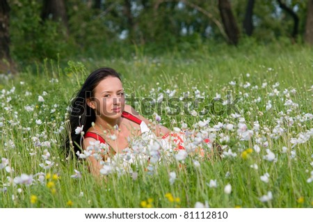 Happy beautiful young woman in green summer flowers field - stock photo