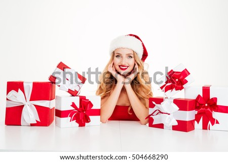 Happy beautiful young woman in santa claus costume with gift boxes over white background