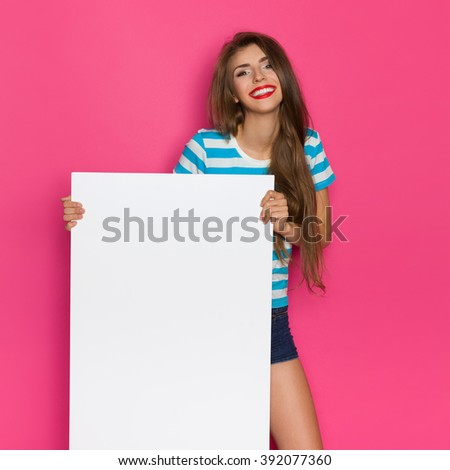 Happy beautiful young woman in striped shirt posing with white poster. Three quarter length studio shot on pink background. - stock photo