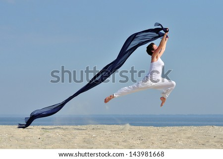 Happy beautiful young woman jumping on the beach with a colored tissue - stock photo