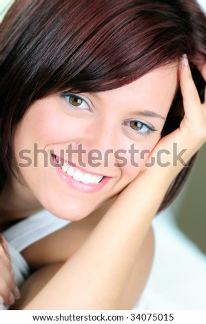 Happy Beautiful Young Woman Relaxing On A Bed Smiling - stock photo