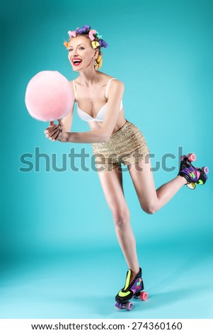 Happy beautiful young woman riding on rollers, eating candy cotton. Blue background. Smiling girl having fun. Summer photo. - stock photo