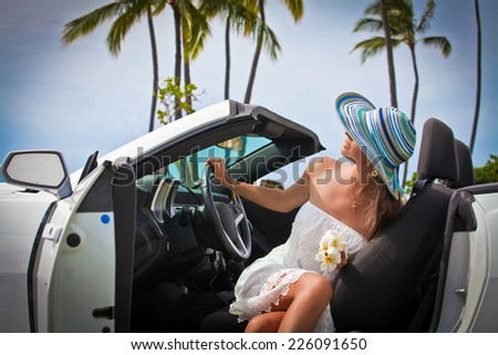 Happy beautiful young woman sitting in a sports car on beautiful sunny summer day. - stock photo