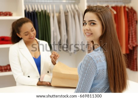 Happy beautiful young woman smiling to the camera over her shoulder helpful shop assistant packing her purchase into shopping bag copyspace service lifestyle shopaholic sale sales seller retail buyer