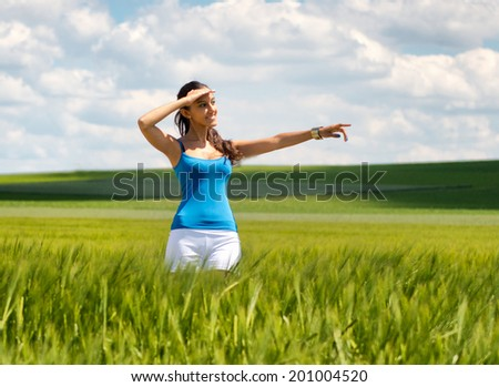 Happy beautiful young woman standing in a field of young green wheat shielding her eyes from the sun and pointing to the right of the frame - stock photo