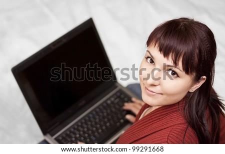 Happy beautiful young woman using laptop - stock photo