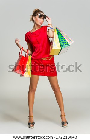 Happy beautiful young woman wearing red dress and sunglasses standing with lots of shopping bags