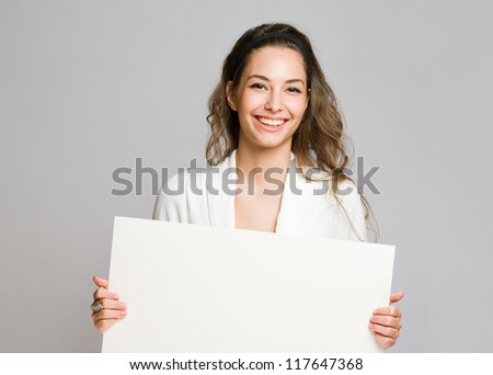 Happy beautiful young woman with empty billboard.