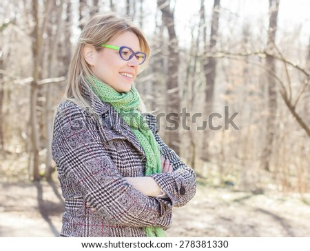 Happy Beautiful Young Woman with glasses portrait in nature. Caucasian female autumn winter season clothing outdoor. - stock photo