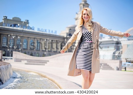 Happy beauty woman in dress walking on the city streets on sunny day - stock photo
