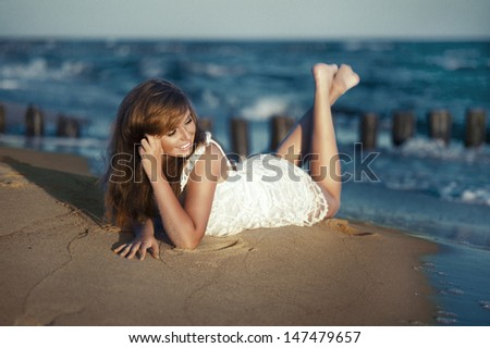 Happy beauty young woman lying on the beach