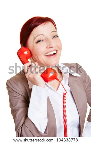 Happy best ager business woman on a red phone receiver - stock photo