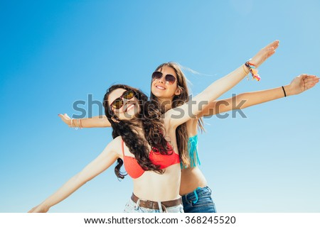 Happy best friends in bikini pretending flying with arms outstretched against a blue sky - stock photo