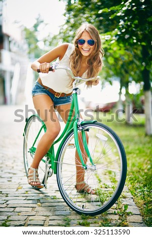 Happy bicyclist in eyeglasses looking at camera in park - stock photo