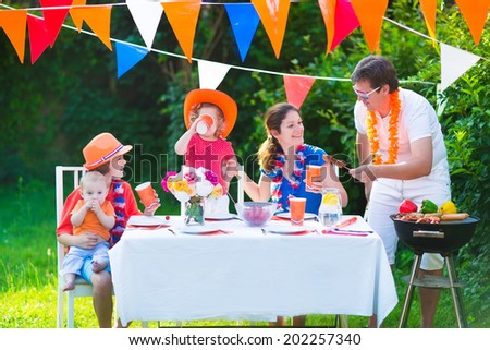 Happy big Dutch family with kids celebrating a national holiday or sport victory having fun at a grill party in a garden decorated with flags of Netherlands, screaming Hup Holland - stock photo