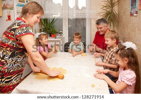 Happy big family cooking a pie together. Father, mother and four children, two boys and two girls playing with dough in the kitchen. - stock photo