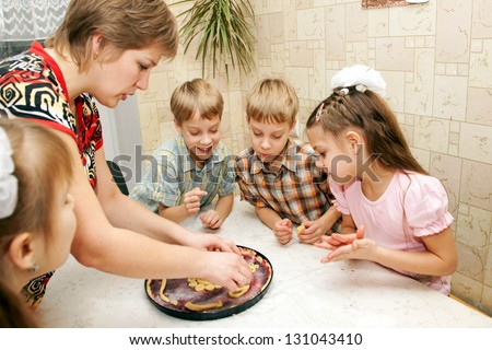 Happy big family cooking a pie together. Mother and four children, two boys and two girls, in the kitchen. - stock photo