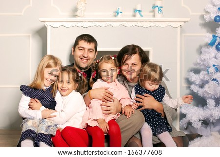 Happy big family hugging near the fireplace and Christmas tree. Father, mother and four children spending time together on Christmas vacation - stock photo