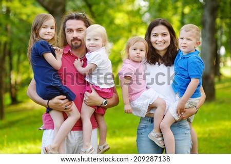 Happy big family of six having fun at summer park on beautiful sunny day - stock photo