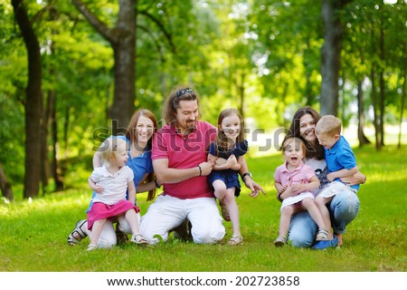 Happy big family of three adults and four kids having fun in summer park - stock photo
