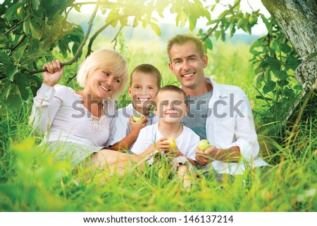 Happy Big Family Outdoors Having Fun. Family with two Children relaxing and Enjoying nature. Outside. Smiling Parents and Kids lying on green grass in the Orchard, Eating Apples and Laughing