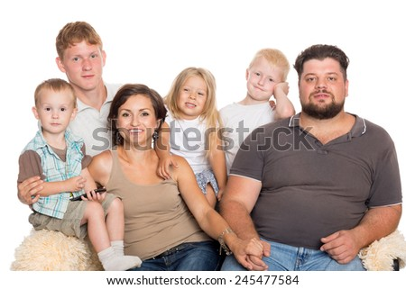 Happy big family sitting on sofa isolated on white - stock photo