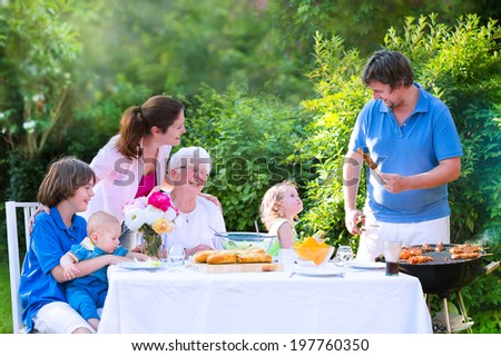 Happy big family - young mother and father with kids, teen age son, cute toddler daughter and a little baby, enjoying BBQ lunch with grandmother eating grilled meat in the garden with salad and bread - stock photo