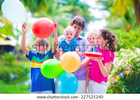 Happy big family, young parents with three children, teenager boy, little toddler girl and adorable baby celebrating birthday party with strawberry cake and balloons in a sunny summer tropical garden - stock photo