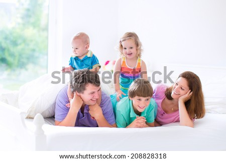 Happy big family, young parents with three kids, laughing boy, cute toddler girl and adorable little baby wearing colorful pajamas reading in bed in a white sunny bedroom at home