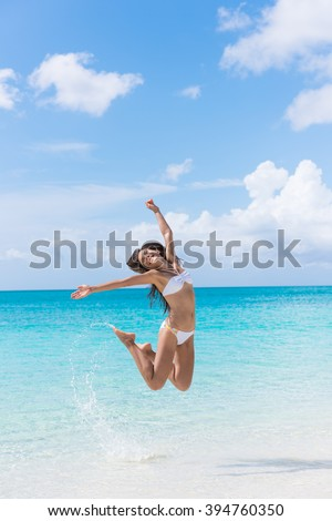 Happy bikini woman having fun jumping of joy and happiness on beach splashing water in perfect turquoise water. Asian girl cheering winning for Caribbean vacation destination during summer travel. - stock photo