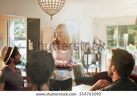 Happy birthday ! Backlit shot of a nice blonde girl in her 30s is bringing the cake with lighted candles, to her friends. They are having fun,  sitting at a wooden table in a charming house. - stock photo