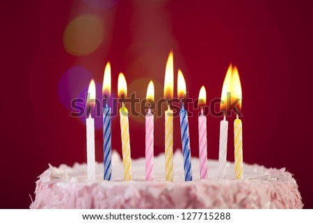 happy birthday cake shot on a red background with candles - stock photo