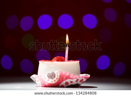 happy birthday cake shot on a red blurred background with candles - stock photo