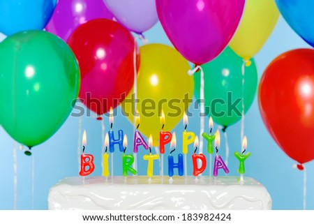 Happy Birthday candle letters on a cake with colourful balloons in the background. - stock photo