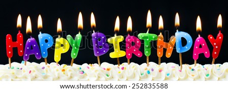 Happy birthday candles against a black background - stock photo
