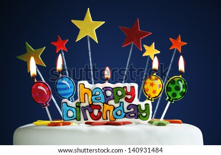 Happy birthday candles and balloons burning on a cake - stock photo