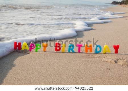 Happy birthday candles on a beach. - stock photo