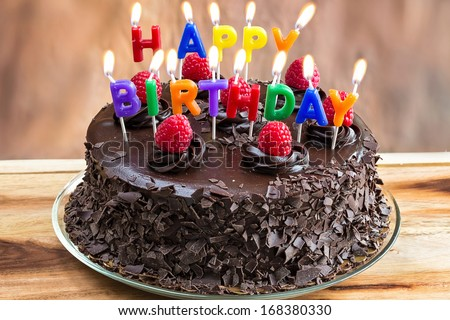 Happy Birthday candles on chocolate cake - stock photo