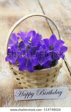 Happy Birthday Card With Wicker Basket Filled Purple Campanula Bell Flowers On Rustic Wooden Surface