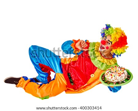 Happy birthday clown holding cake and lying on the floor.  Isolated. - stock photo